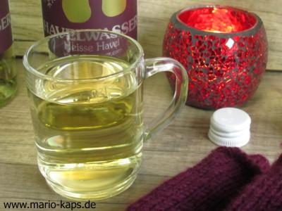 Heisse Havel weiß im Punschglas mit rotem Teelichtglas und Flaschen im Hintergrund