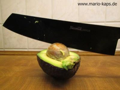Kern aus einer Avocadohälfte mit Hilfe des Messers entfernen