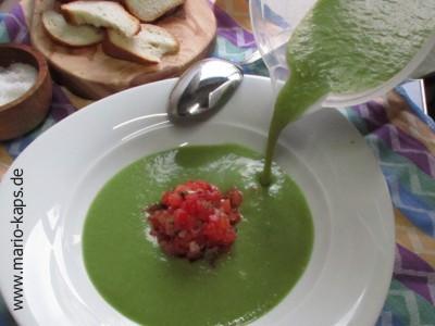 Green Gazpacho - Gazpacho mit Messbecher in einen tiefen Teller gießen, in dem sich ein Haufen mit Tomaten-Kapern-Salat befindet